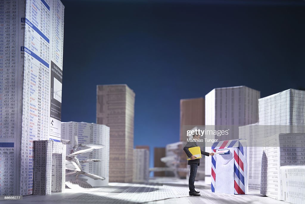 Man posting letter in a city of newspaper : Stock Photo