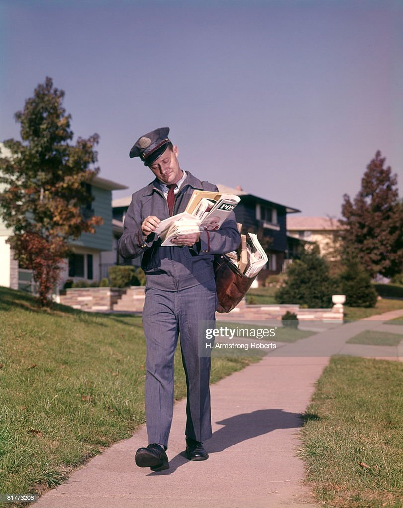 Man Postman Delivering Mail In Suburban Neighborhood Sorting Letters Walking On Sidewalk. : Stock Photo