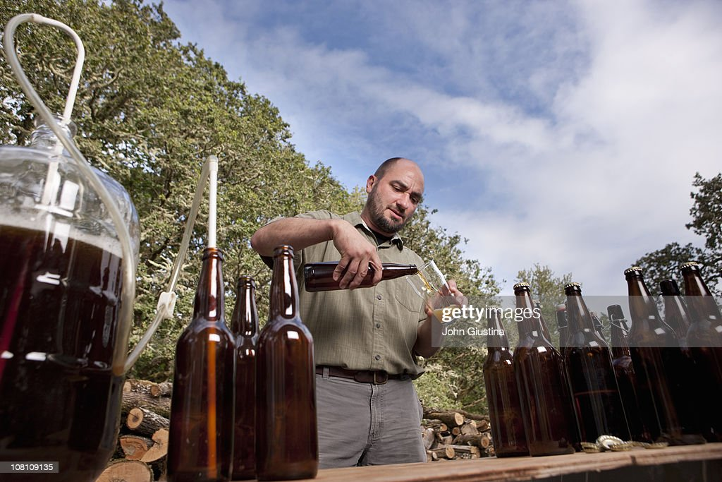 Man pouring a beer for himself. : Stock Photo