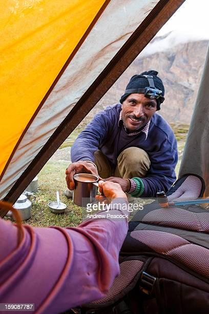 A man pouring a cup of tea in camp