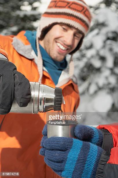 Man pouring a drink from a thermos