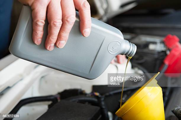 Man pouring car oil from plastic bottle