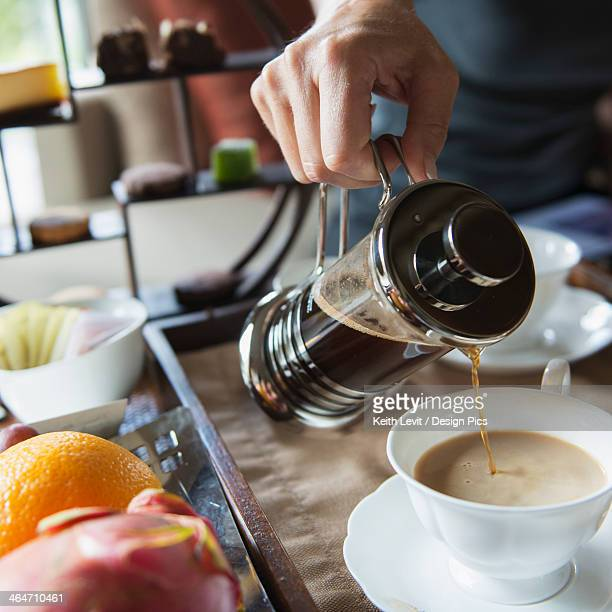 Man pouring coffee into a cup from a coffee press