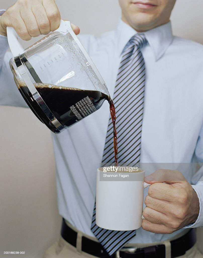 Man pouring coffee into mug, mid section : Stock Photo