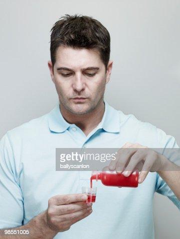 Man Pouring Cough Medicine into Measuring Cup. : Stock Photo