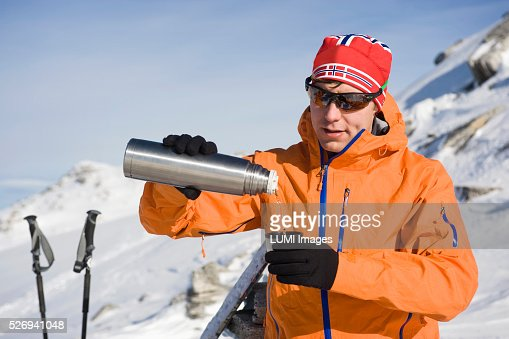 Man pouring from vacuum flask in mountain landscape, Weissenseegletscher, Salzburg, Austria : Foto de stock