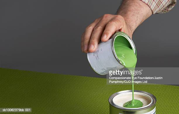 Man pouring paint into another paint can, close-up of hand, studio shot, elevated view