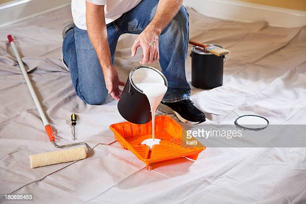 Man pouring paint into tray
