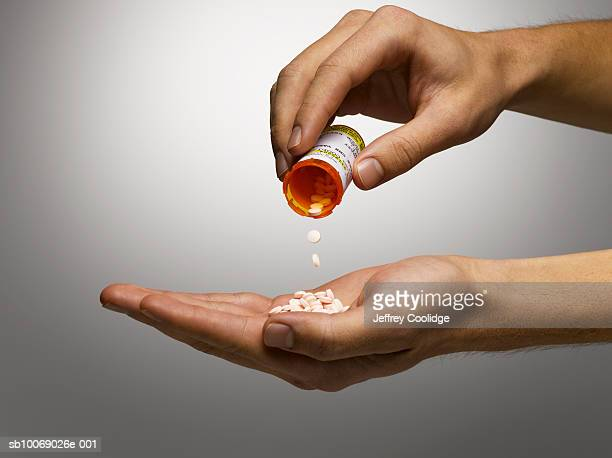 Man pouring prescription pills into hand, close-up, studio shot
