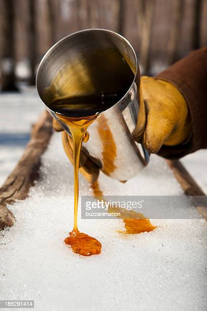 Man pouring syrup from a tin cup into the snow