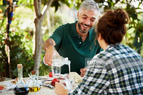 Man pouring water for colleague in yard