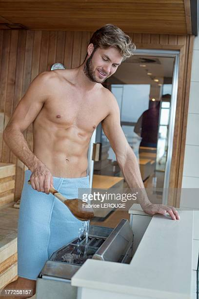 Man pouring water on coal in a sauna