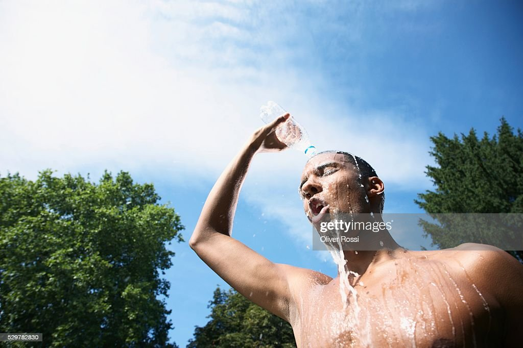Man Pouring Water on Himself : Stockfoto