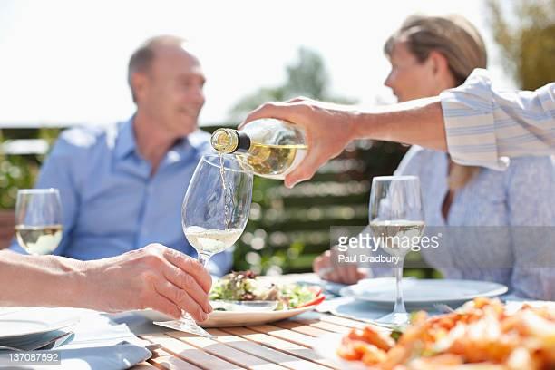 Homme, verser le vin dans la ville ensoleillée de table