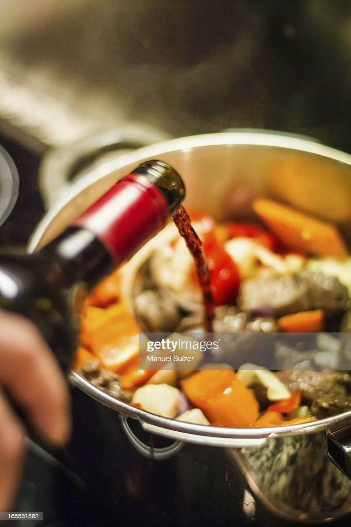 Man pouring wine into vegetables