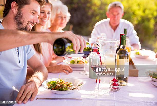 Man pouring wine while enjoying a family meal
