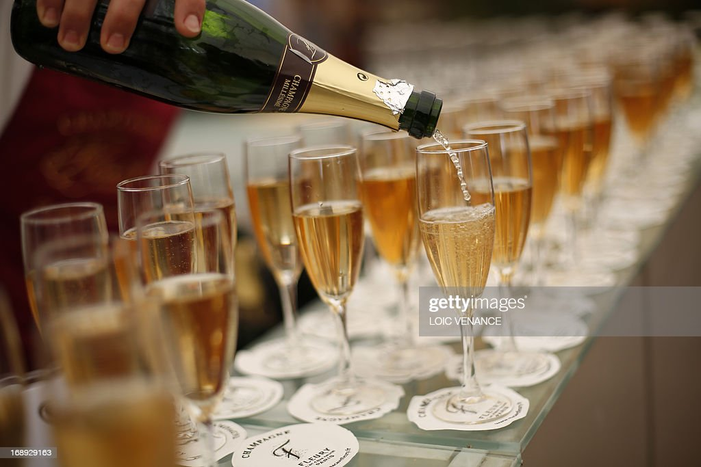 A man pours champagne in glasses at a beach bar set up along the Croisette during the 66th edition of the Cannes Film Festival in Cannes on May 17, 2013.