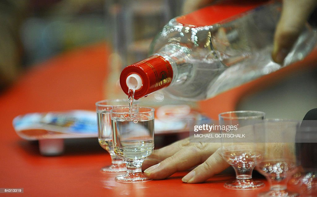 A man pours glasses of Russian Vodka as final preparations are under way for the International Green Week Food and Agriculture Trade Fair in Berlin...