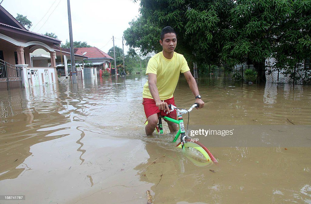 A man powers his bicycle through the flood waters in Malaysia's Terengganu state on December 27, 2012. Floods triggered by torrential monsoon rains in Malaysia have claimed the life of a second victim although waters have subsided, allowing some evacuees to return home from relief centres, reports said. MALAYSIA