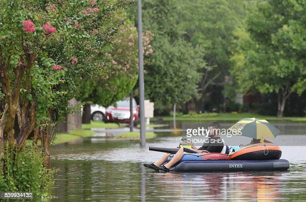 A man powers his boat with a leaf blower as he floats around flood water on Apple Street in Pearland on August 27 2017 as the US fourth city city...
