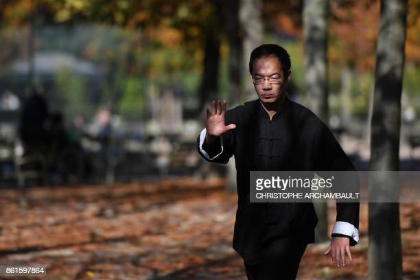 A man practices Chinese martial art taichi at the Jardin du Luxembourg in Paris on October 15 2017 during unusually warm autumnal temperatures / AFP...