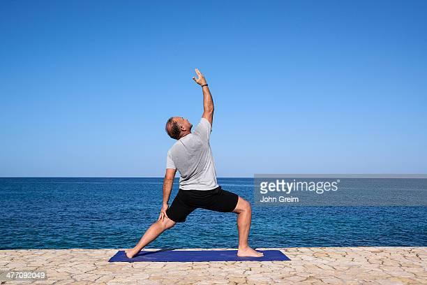 Man practices morning yoga at a seaside spa