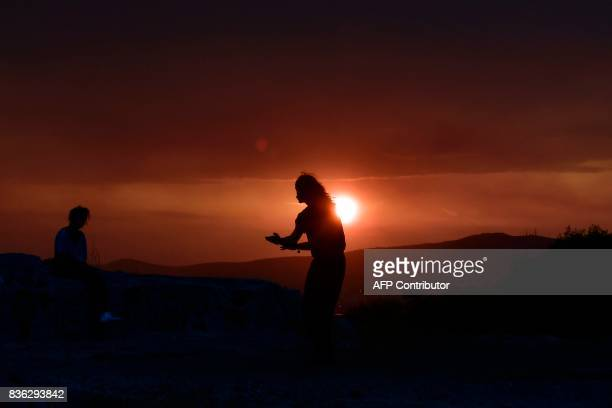 A man practices Tai Chi at sunset on Filipappou hill in Athens as heavy rain cloud hang over the city on August 21 2017 / AFP PHOTO / LOUISA...