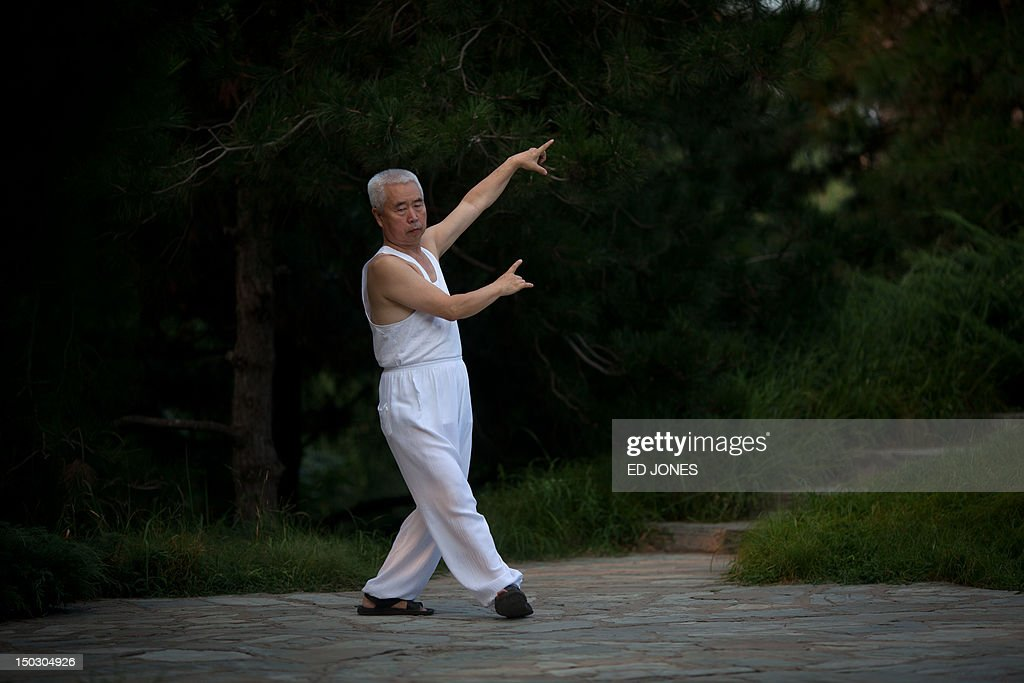 A man practices T'ai Chi in a park in Beijing on August 15, 2012. T'ai chi is a popular form of internal Chinese martial art practiced for its defence training and health benefits. AFP PHOTO / Ed Jones
