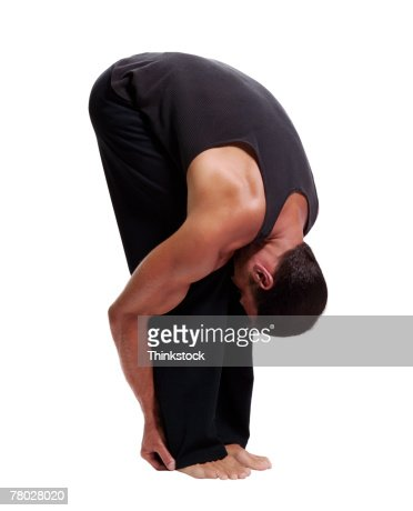 A man practices yoga, bending at the waist and grasping his legs : Stock Photo
