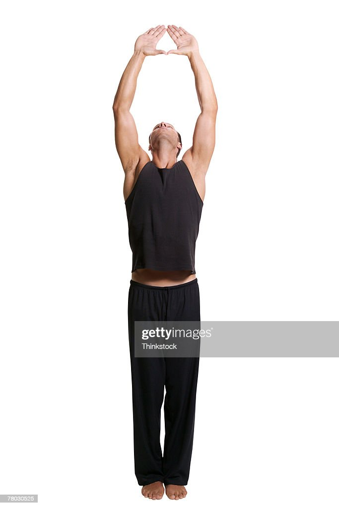 A man practices yoga, with his arms reaching high above him