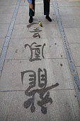 A man practicing calligraphy with water on a pathway in Beihai Park an imperial garden to the northwest of the Forbidden City in Beijing China First...
