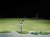 Man practicing golf on  driving range at night