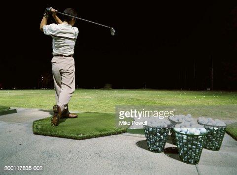 Man practicing golf on  driving range at night, rear view
