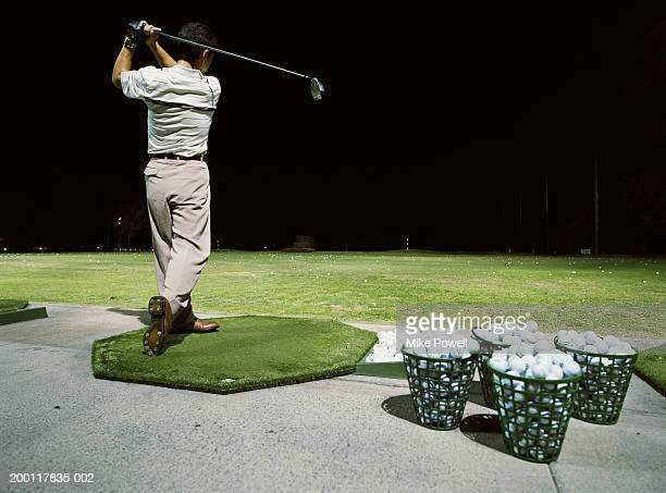 Man practicing golf on  driving range at night, rear view