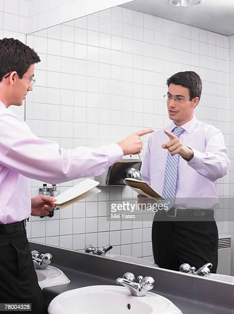 Man practicing speech in office washroom mirror