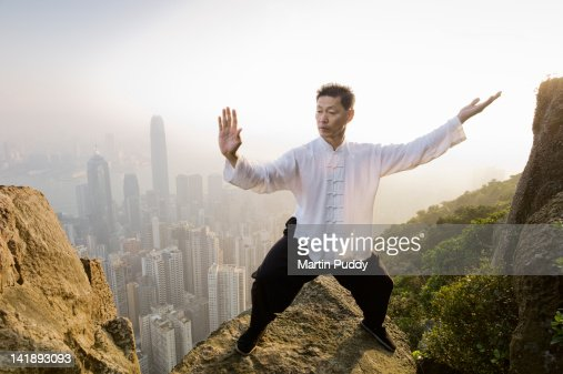 Man practicing Tai Chi infront of skyline