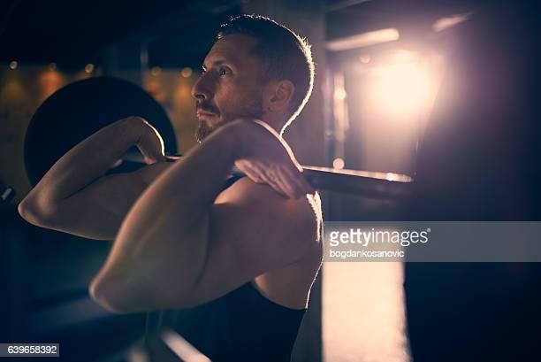 Homme pratiquant le poids et haltères