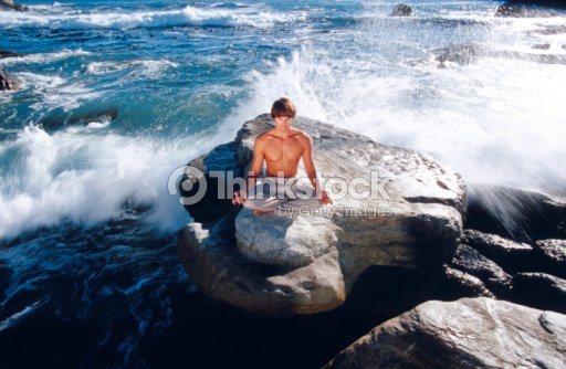Man practicing yoga by ocean : Stock Photo