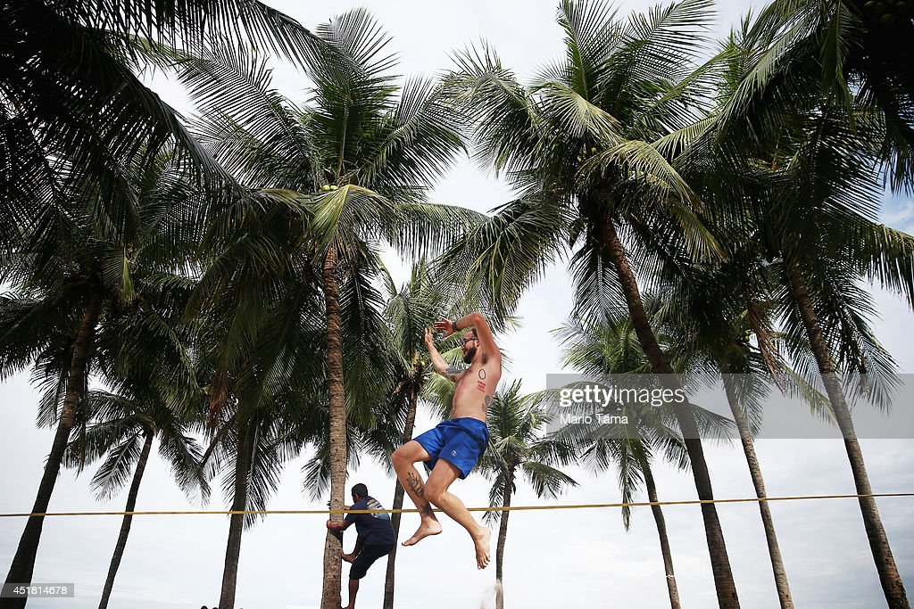 A man practises slacklining as another climbs a tree on Copacabana Beach on July 7, 2014 in Rio de Janeiro, Brazil. Brazil plays Germany tomorrow in the first semi-final match of the 2014 FIFA World Cup.