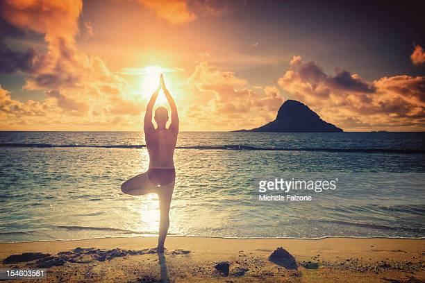 A man practising yoga by the sea at sunrise