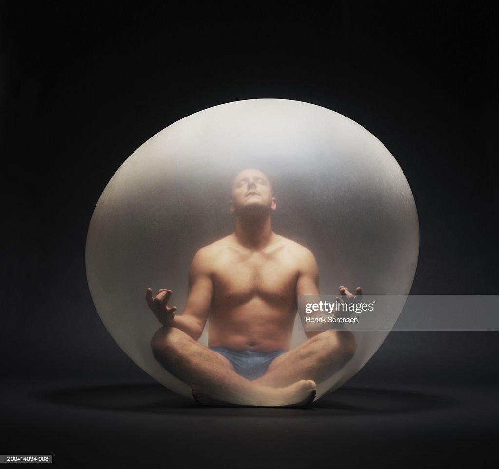 Man practising yoga inside inflated balloon : Stock Photo