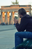 Man praying at Brandenburg Gate, Berlin