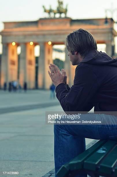 Man praying at Brandenburg Gate, Berlin