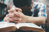 Religion, Christianity, Praying.  Man praying, hands clasped together on her Bible.