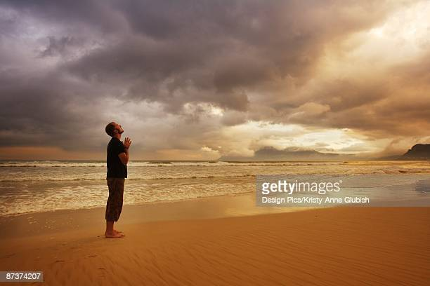 Man praying on a beach