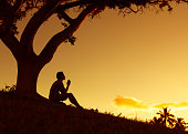 Male sitting under a tree clasping his hands together.  (Praying and feeling desperate concept)