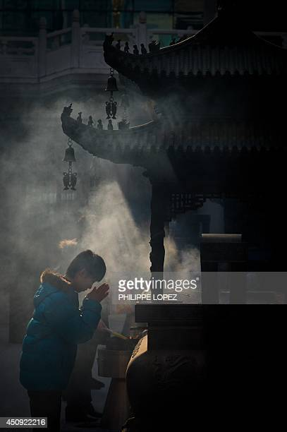 A man prays after burning incense sticks at a temple in Shanghai on January 31 2011 ahead of the Lunar New Year China's 13 billion inhabitants will...