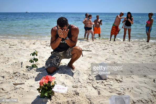 A man prays after laying flowers on Marhaba beach where 38 people were killed on Friday in a terrorist attack on June 28 2015 in Souuse Tunisia...