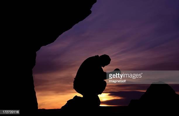 Man prays against beautiful sunset on Mountain