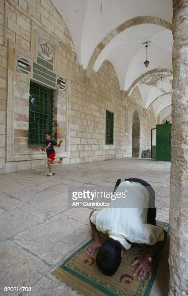 A man prays as a young boy runs past the tomb of the late King Abdullah I greatgrandfather of Jordanian monarch Abdullah II inside Jerusalem's alAqsa...